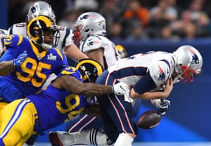 New England Patriots quarterback Tom Brady (12) is tackled by Los Angeles Rams defensive end John Franklin-Myers (94) during the first quarter in Super Bowl LIII at Mercedes-Benz Stadium.
