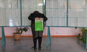 A woman reads lists of electors at a polling station in the village of Baytik, 20 km outside the capital Bishkek.