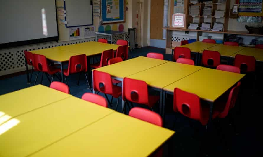 Red chairs and yellow tables in an empty classroom.