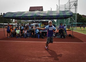 A man in the 75-80 age category competing in the javelin