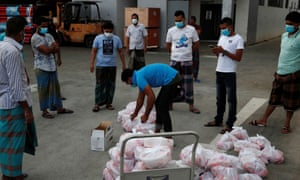 Migrant workers living in a factory-converted dormitory collect meals donated by charities for their Eid-al-Fitr celebrations.