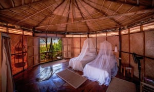 Two beds inside a thatched cabana.