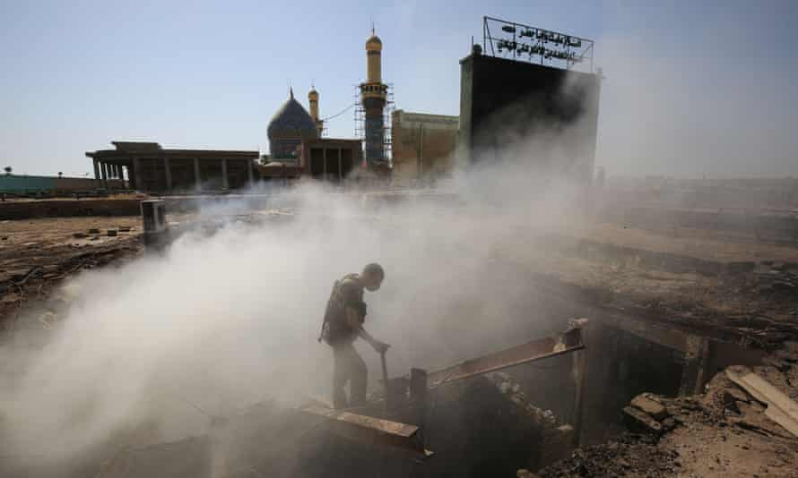 TOPSHOT - An Iraqi policeman inspects the aftermath scene of a mortar and bombing attack on the Sayyid Mohammed shrine in the Balad area, located 70 kilometres (around 45 miles) north of Baghdad, on July 8, 2016. Islamic State group militants killed 30 people at the Shiite shrine, striking the area with suicide bombers, gunfire and mortar rounds, an Iraqi security spokesman said. The attack came just five days after a suicide bomber detonated an explosives-rigged minibus in the capital, killing 292 people. / AFP PHOTO / Ahmad al-RubayeAHMAD AL-RUBAYE/AFP/Getty Images