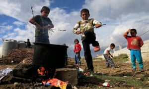 Syrian refugee boys help make a fire to boil water outside their family's tent at a refugee camp in the Bekaa valley, Lebanon