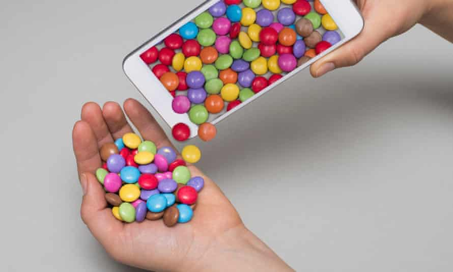 Brightly coloured sweets pouring out of a phone into a hand