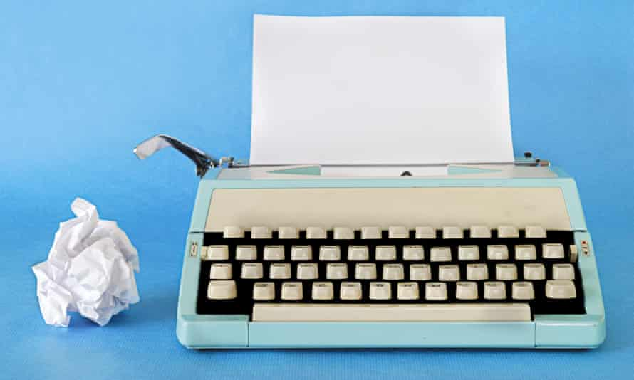 Retro TypewriterManual Typewriter Circa 1970 with a blank sheet of paper and rejected work alongside