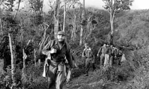 Fidel Castro with bag and gun in the Sierra Maestra, Cuba, in 1963.