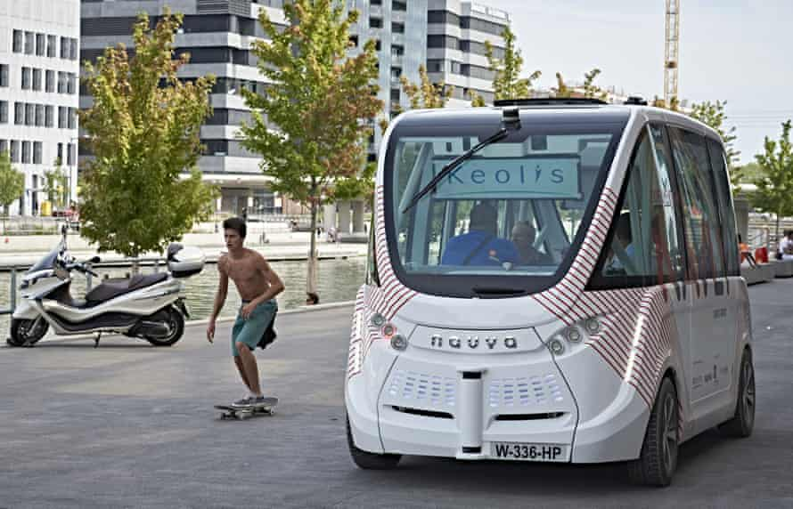 A skateboarder rides next to an electric driverless bus in Lyon, France.