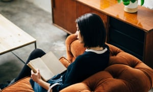 Brunette young girl reading on an orange velvet chester sofa in an industrial loft