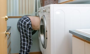 A man with his head in a washing machine