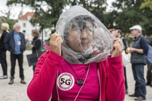 A woman wears a protective shield and a protest sticker against 5G technology in The Hague, the Netherlands