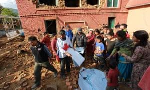 Members of the Red Cross distribute tarpaulins to displaced residents in Kathmandu