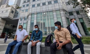 A group of men wearing masks sit on a bench in the financial district of Singapore, 16 February 2021.