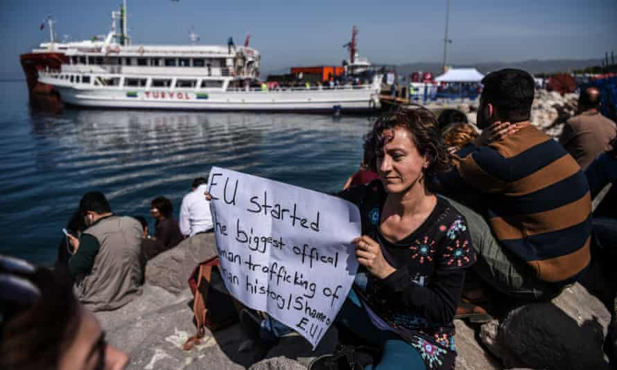 A woman holds a placard as a ferry carrying migrants being deported to Turkey arrives at the port of Dikili in Izmir