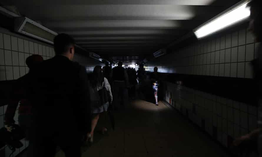 People walk in darkness at Clapham Junction station in London during last month's power cut