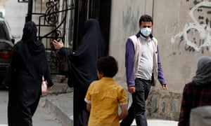 A Yemeni man wearing a protective face mask walks through a neighborhood in Sana'a, Yemen