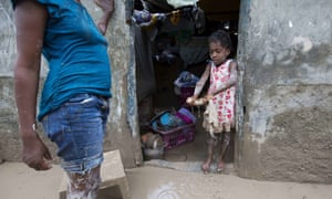 A girl helps her mother to remove mud from her house after Hurricane Matthew flooded their home in Les Cayes, Haiti, Thursday, Oct. 6, 2016