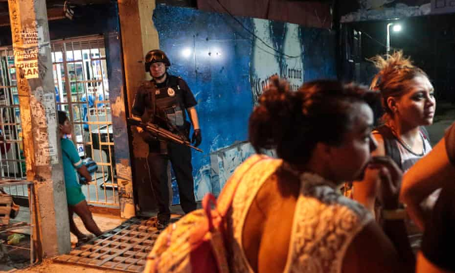 A Federal Police officer stands at the entrance of a bar where a man was shot dead by gunmen in Acapulco