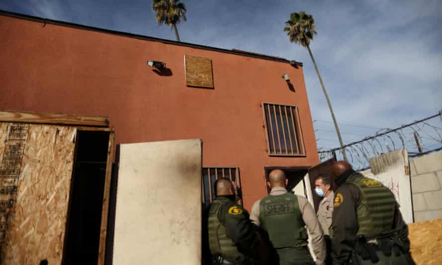 Los Angeles sheriff's deputies walk up to a commercial building to carry out an eviction order, 13 January 2021.