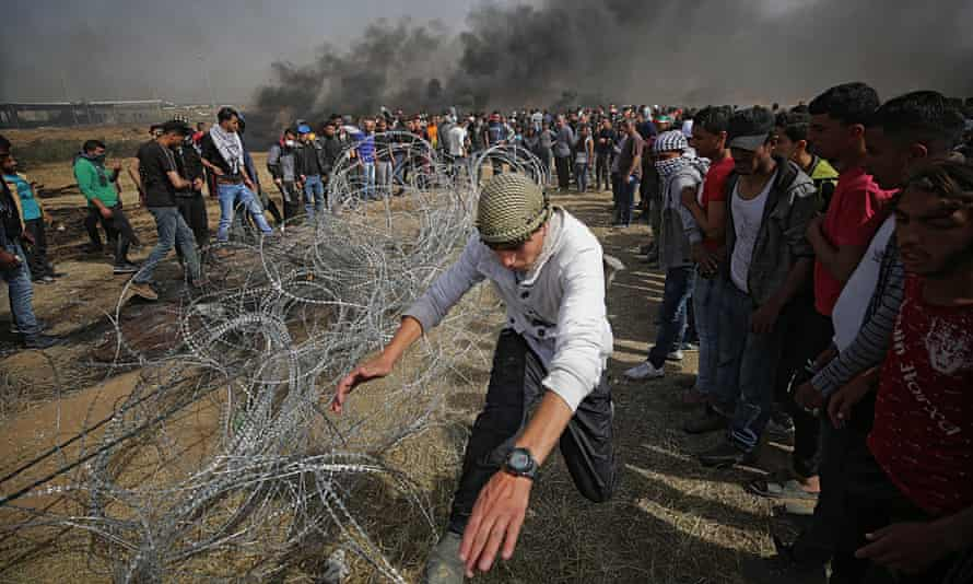 A protester pulls a barbed wire fence near the border with Israel. There are clouds of black smoke in the background
