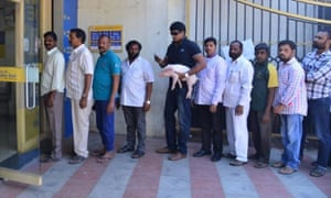 Actor Ravi Babu queues outside an ATM in Hyderabad with a piglet