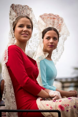 Two young women wear traditional lace mantillas