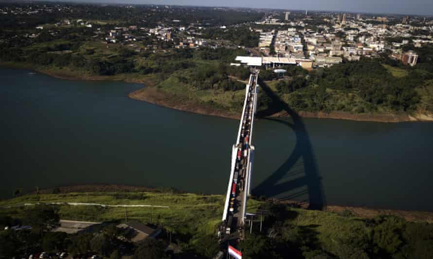 Trucks wait in line on Friendship Bridge over the Paraná River, the natural border between Foz do Iguazu, Brazil, top, and Ciudad del Este, Paraguay, during the COVID-19 quarantine on 23 June.