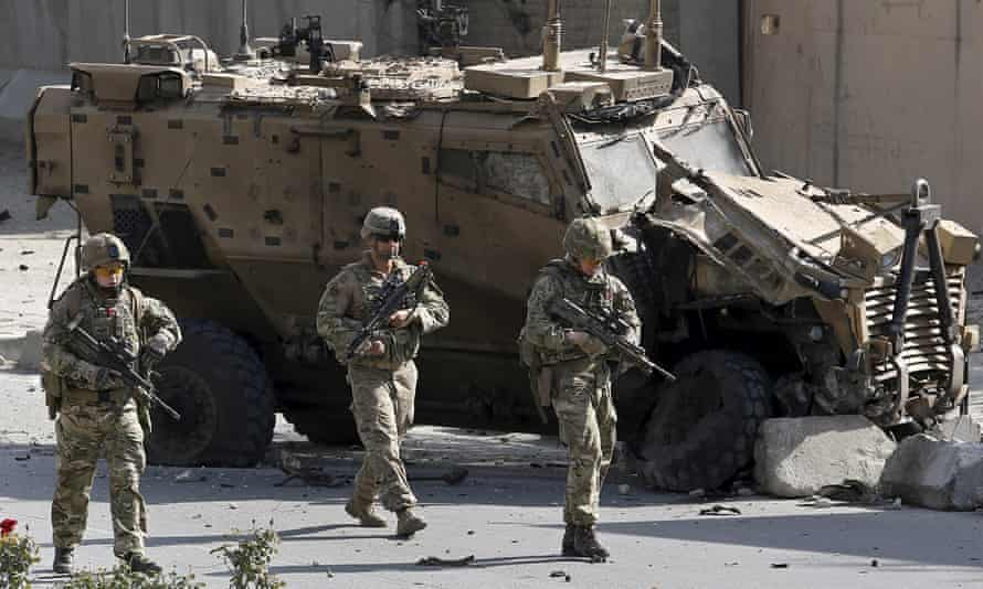 Nato soldiers walk in front of a damaged military vehicle last year in Kabul, Afghanistan.