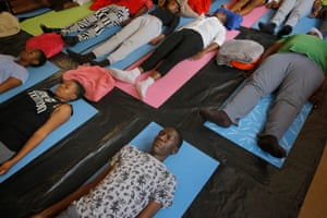 Children lie in 'savasana' or 'corpse' pose at the end of their afternoon yoga class.