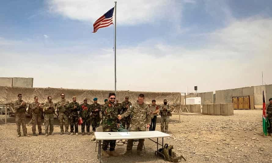 A US soldier and an Afghan soldier shake hands during a handover ceremony to the Afghan army at Antonik camp in Helmand province, Afghanistan, on 2 May.