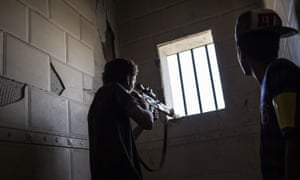 A fighter of the Libyan forces affiliated to the Tripoli government shoots against Islamic State positions, in Sirte, Libya.