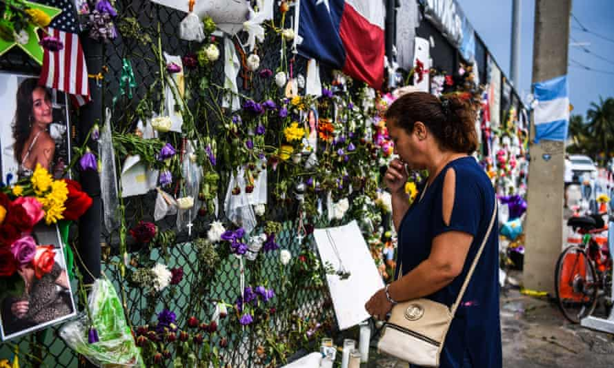 A woman prays as she visits a makeshift memorial where the partially collapsed Champlain Towers South building stood in Surfside, Florida.