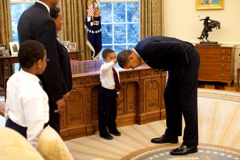 President Barack Obama bends over so the son of a White House staff member can pat his head during a visit to the Oval Office in 2009.