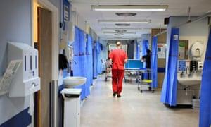 An NHS worker walks down a hospital corridor
