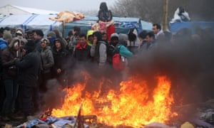 Migrants and activists stand around a fire as the demolition of the main Calais refugee camp continues.