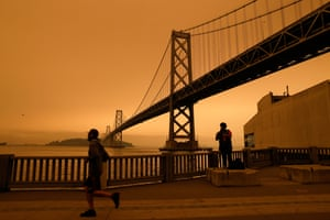 A view of the San Francisco Bay Bridge under an orange overcast sky in the afternoon.