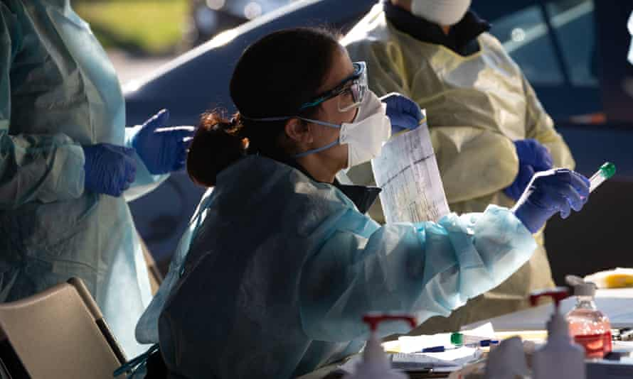 A member of the Covid-19 DHS testing team holds a vile with a swab from a test conducted at a pop-up testing facility in the suburb of Broadmeadows on Sunday.