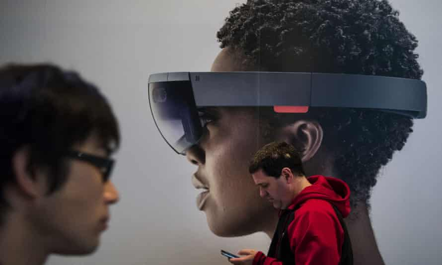 A man checks his phone standing in front of a poster of the Microsoft HoloLens. Half of the elevators in the US are over 20 years old, according to a ThyssenKrupp executive, and the HoloLens promises to make repairs easier.
