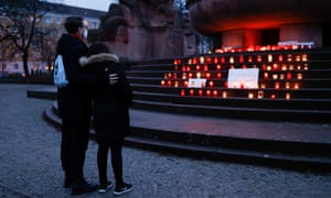 People pay their respects at a memorial site for those who have died from the novel coronavirus Covid-19 at Arnswalder Platz, in Berlin's Prenzlauer Berg district.