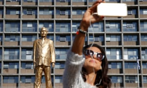 woman takes a selfie with the golden Netanyahu statue
