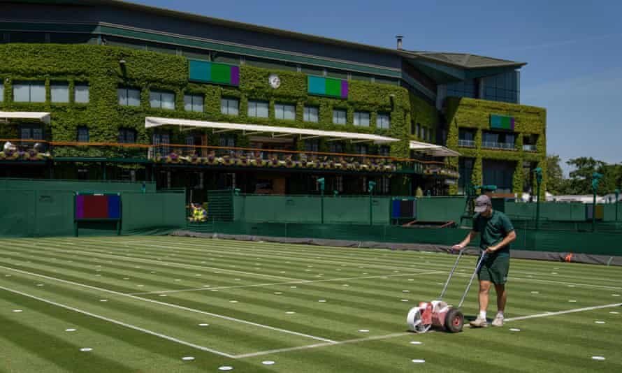 Ground staff mark out the lines as preparations continue at the All England Club for Wimbledon