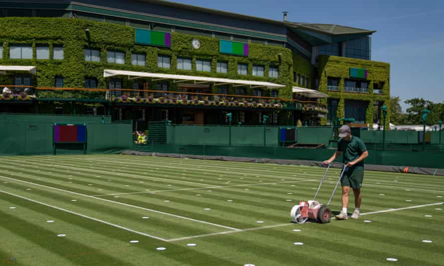 Ground staff mark out lines on a court at the All England Lawn Tennis Club, Wimbledon.