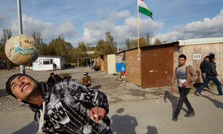 People play football at a government-approved refugee camp near Dunkirk