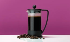 French press coffee pot on a table with coffee beans against a pink background