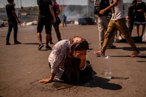 A woman cleans her eyes with water after police fired teargas at migrants who threw stones during a protest to demand shelter after the Moria camp burned down.