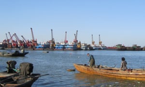 Fishers on Lake Poyang look out at industrial sand dredging boats.