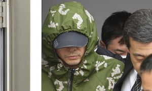 Yasuo Yamamoto is escorted out Obama Police Station in Obama, Fukui prefecture, western Japan on Saturday.