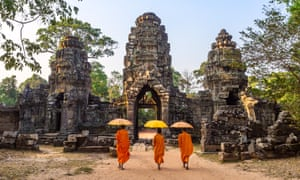 Buddhist monks walking inside Angkor Wat templeThree buddhist monks with umbrellas, walking inside Angkor Wat temple. Siem Reap, Cambodia