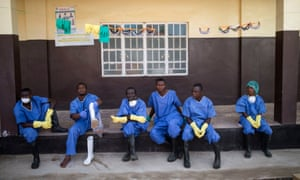 Health workers resting outside a quarantine zone at a Red Cross facility in the town of Koidu, Sierra Leone, in December 2014