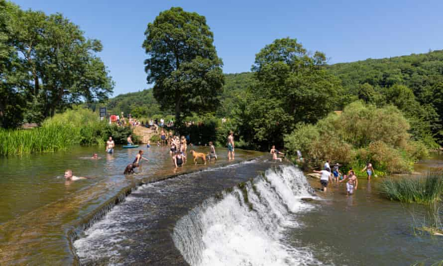 People swimming at Warleigh Weir, a popular wild swimming spot near Claverton in Somerset, in 2018